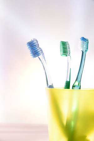 daily family dental cleaning with yellow plastic cup with toothbrushes. Vertical composition. Front view.