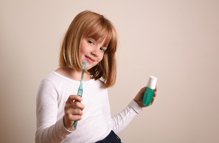 Girl showing toothbrush and toothpaste on brown isolated background. Horizontal composition.