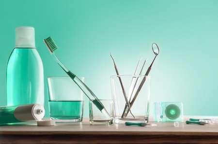 Tools for oral hygiene on wooden table with green background. Horizontal composition. Front view.
