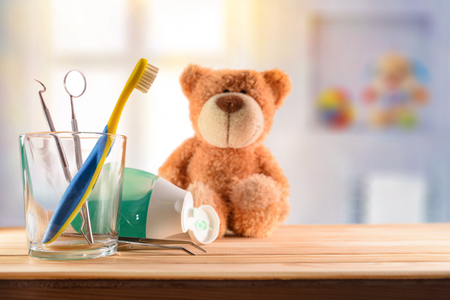 Dentist concept for children with tools in glass cup and teddy on wooden table in room with toys background. Horizontal composition. Front view Stock Photo