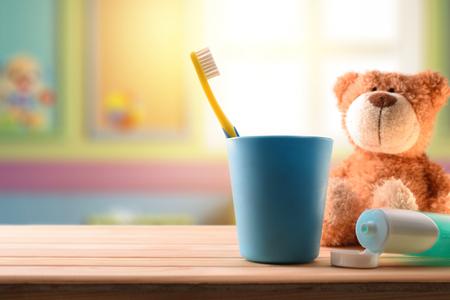 Mundhygiene für Kinder im Kinderzimmer mit Reinigungselementen auf Holztisch und Stofftier. Horizontale Komposition. Vorderansicht