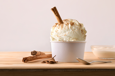 Cinnamon ice cream decorated with cinnamon sticks on a wooden table. Horizontal composition. Front view. Imagens
