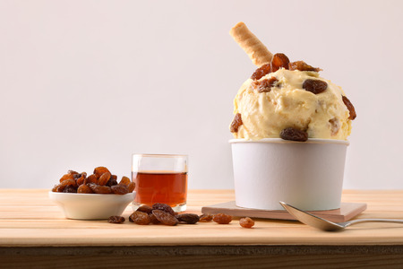 Rum with raisins ice cream cup decorated with raisins on a wooden table. Horizontal composition. Front view.