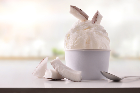 Coconut ice cream cup on white table homemade with kitchen background. Horizontal composition. Front view.