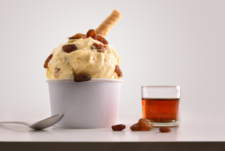 Composition of raisins ice cream ball in paper cup on white table with products of ornament and elaboration isolated background. Horizontal composition. Front view.