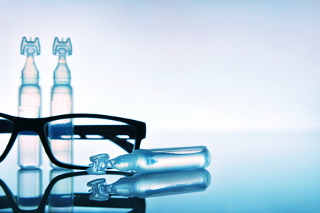 Artificial tears eye drops encapsulated in plastic pipettes with eye glasses reflected on glass table with blue background. Horizontal composition. Front view.