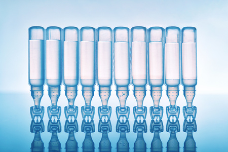 Artificial tears eye drops encapsulated in plastic pipettes and reflected on glass table with blue background. Horizontal composition. Front view upside down