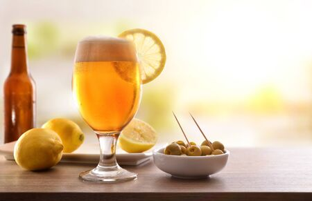 Glass of beer with lemon with appetizer on wooden table. Horizontal composition. Front view Stok Fotoğraf