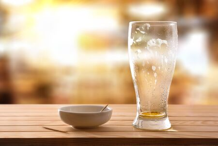 Finished drinking beer glass and empty snack container on wooden slatted table in a local. Horizontal composition. Front view.
