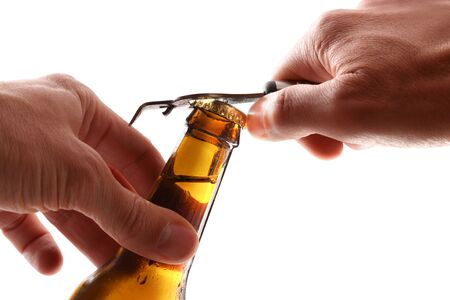 Detail of hands about to open a beer can with a bottle opener with white background.  Horizontal composition. Front view.