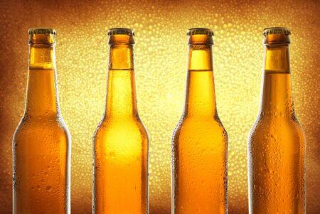 Fila de cuatro botellas de vidrio cerradas con cerveza fresca sobre fondo dorado. Composición horizontal. Vista frontal.
