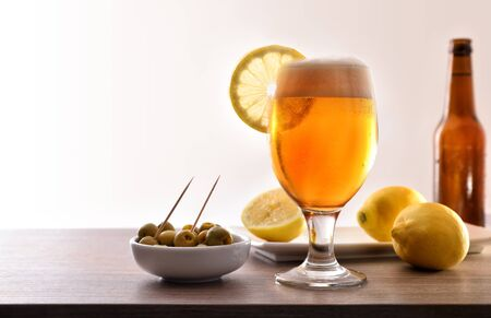 Glass of beer with lemon with appetizer on wooden table with white background. Horizontal composition. Front view