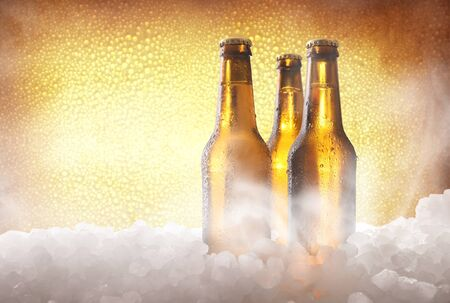 Three full beer bottles on crushed ice and golden background . Horizontal composition. Front view.