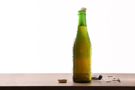 Green glass bottle with sparkling liquid and white background. Horizontal composition. Front view.