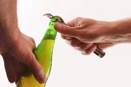 Opening a green glass bottle with a metal bottle opener and white isolated background.  Horizontal composition. Front view.