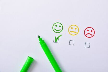 Satisfaction positive marquée avec un marqueur vert représenté par des émoticônes colorées sur du papier blanc. Composition horizontale. Vue de dessus.