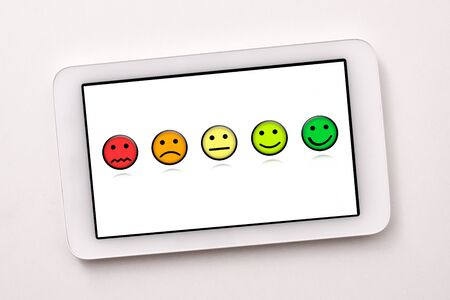 Satisfaction representation levels with emoticons on white tablet screen on white table close up. Horizontal composition. Top view. Imagens