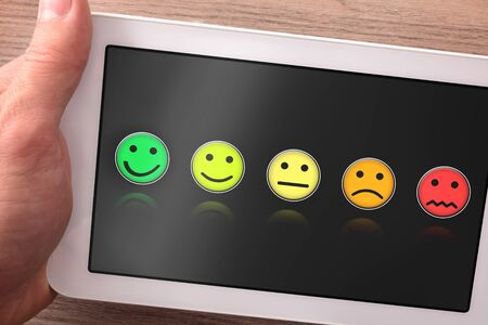 Evaluation on the satisfaction of a service or product on a tablet represented with faces of expression. Horizontal composition. Top view. Stockfoto