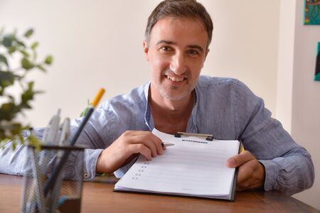 Man in blue striped shirt showing a questionnaire on a wooden table in a room. Horizontal composition. Front view.