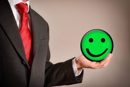Businessman with smiley emoticon in a hand. Success concept. Horizontal composition. Side view.