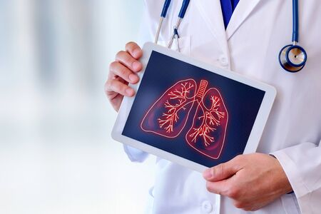 Doctor showing a picture of lungs on a tablet in a hospital. Horizontal composition.