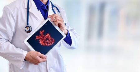 Doctor showing a picture of a heart on a tablet in a hospital. Horizontal composition.