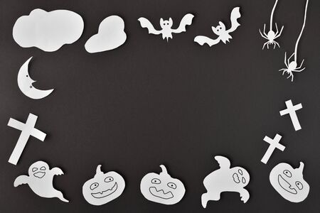 Halloween craft background with white paper cutouts on black cardboard. Horizontal composition.