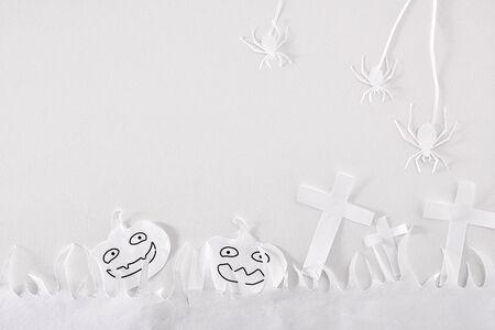 Fun Halloween composition with paper cutouts on white table. Horizontal composition.