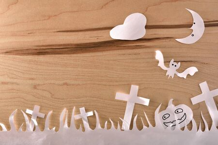 Halloween craft with white paper cutouts on wooden table. Horizontal composition. Stok Fotoğraf