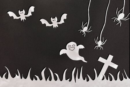 Halloween composition with white paper cutouts on black cardboard detail. Horizontal composition.