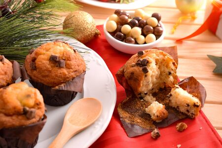 Freshly baked chocolate chip muffin on wooden table decorated with Christmas objects. Horizontal composition. Elevated view.