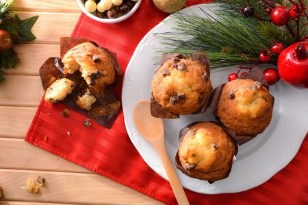 Freshly baked chocolate chip muffin on wooden table decorated with Christmas objects. Horizontal composition. Top view.