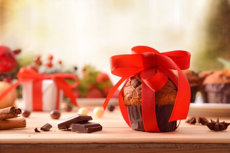 Chocolate chip muffin on wooden table decorated with Christmas objects with red bow. Horizontal composition. Front view.
