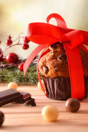 Chocolate chip muffin on wooden table decorated with Christmas objects with red bow. Vertical composition. Front view.