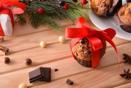 Chocolate chip muffin on wooden table decorated with Christmas objects with red bow. Horizontal composition. Elevated view.