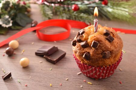 Chocolate muffin with red white polka dot paper and lit candle on table with portions and decorated chocolate balls and green branches. Horizontal composition. Elevated view. Zdjęcie Seryjne