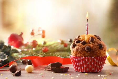 Chocolate muffin with red white polka dot paper and lit candle on table with portions and decorated chocolate balls and green branches. Horizontal composition. Front view.
