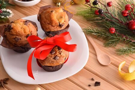 Chocolate chip muffin on white plate on wooden table decorated with Christmas objects with red bow. Horizontal composition. Elevated view.