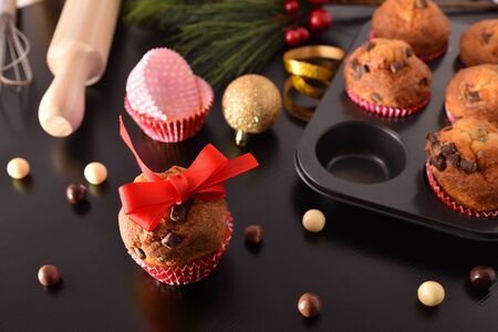 Freshly homemade chocolate muffins for Christmas parties on black table with decoration and kitchen items. Horizontal composition. Elevated view.