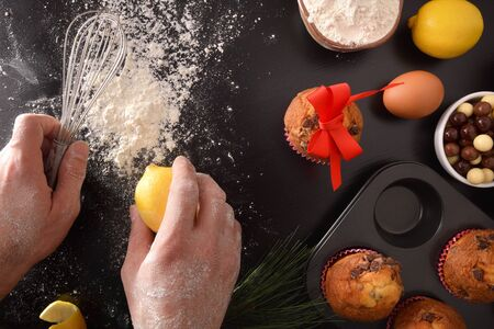 Making chocolate muffins for celebrations with hands and kitchen utensils and products for the elaboration. Horizontal composition. Top view. Zdjęcie Seryjne