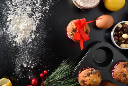Background with elaboration of muffins for the christmas holidays on black table with lemos and eggs with scattered flour. Horizontal composition. Top view.