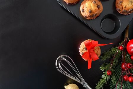 Background with freshly muffins for the christmas holidays on black table. Horizontal composition. Top view.