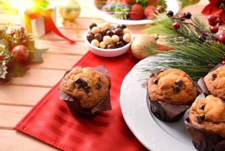 Muffins with chocolate chips on wooden table decorated with christmas objects. Horizontal composition. Elevated view. Zdjęcie Seryjne