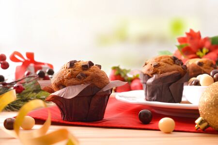 Muffins with chocolate chips on wooden table decorated with christmas objects. Horizontal composition. Front view.