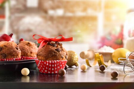 Christmas table with freshly baked muffins with traditional cuisine in the background. Horizontal composition. Front view.