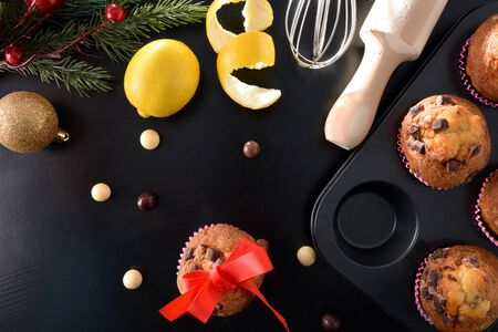 Freshly homemade chocolate muffins for Christmas parties on black table with lemos and kitchen items. Horizontal composition. Top view. Zdjęcie Seryjne