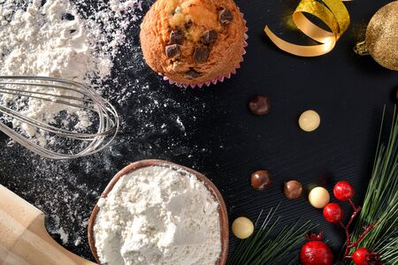 Background with elaboration of muffins for the christmas holidays on black table with ingredients and tools and scattered flour. Horizontal composition. Top view.