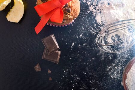 Preparation of desserts for holidays with muffin and ingredients on black table. Horizontal composition. Top view. Zdjęcie Seryjne