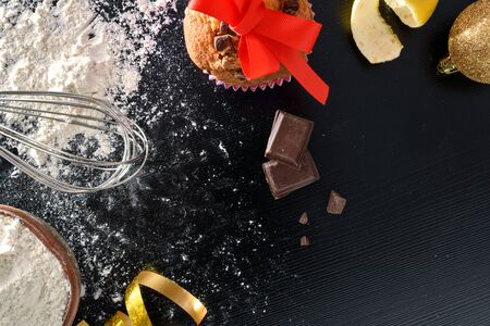 Background with ingredients for preparation of muffins at Christmas on black table with tools and scattered flour. Horizontal composition. Top view.