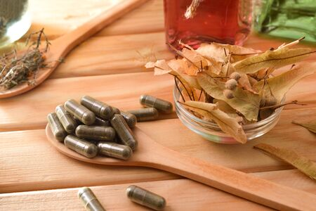 Capsules and bottles of essence of natural medicine with medicinal plants on wooden table. Elevated view. Horizontal composition.